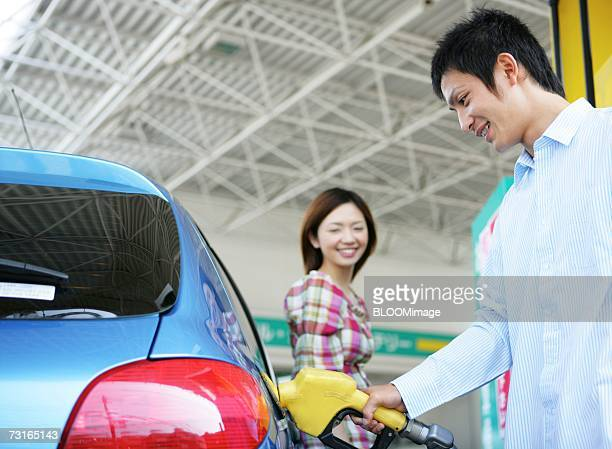 Man standing holding a petrol pump nozzle with girlfriend