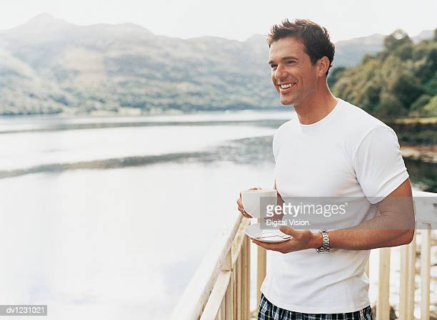 Man Standing Holding Coffee Cup and Saucer Next to Railing Beside a Lake Smiling