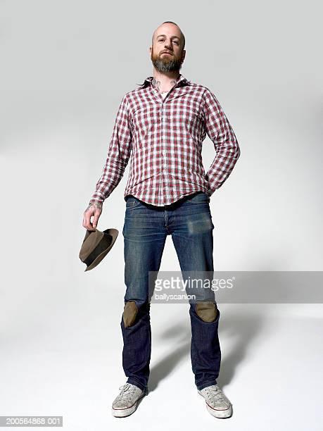 Man standing, holding hat, portrait