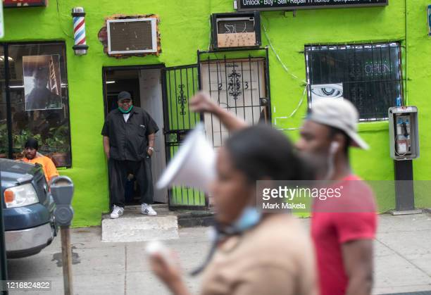 A man standing in a barber shop observes protesters marching after widespread unrest following the death of George Floyd on June 1 2020 in...