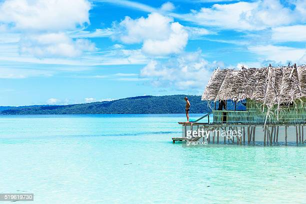 man standing in a beach hut by the sea - raja ampat islands stock photos and pictures