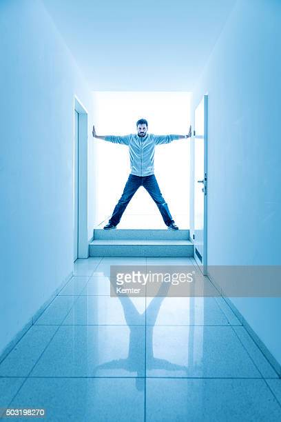 man standing in a bright corridor