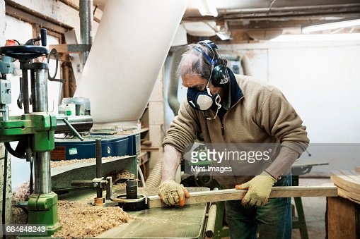 Man standing in a carpentry workshop, wearing a respirator and hearing protector, working on a piece of wood.