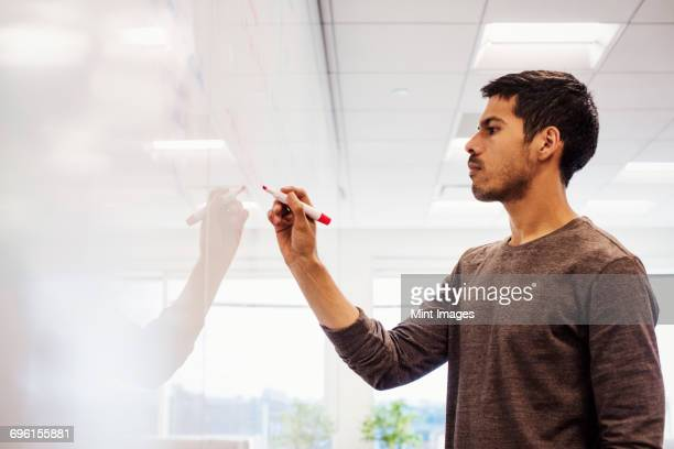 A man standing in a classroom writing on a whiteboard.