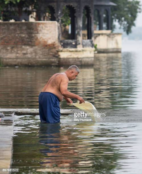 A man standing in a lake in India washing his clothes by hand.