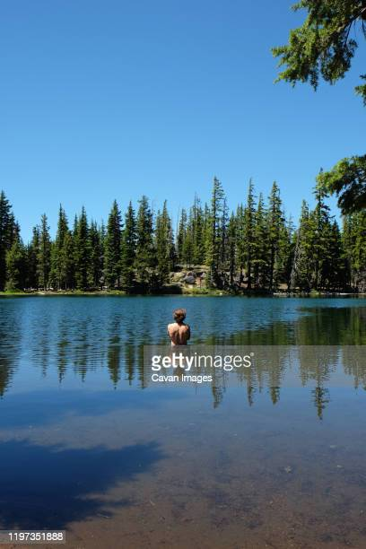 man standing in a lake with reflections of body, trees, and sky - deschutes national forest stock pictures, royalty-free photos & images