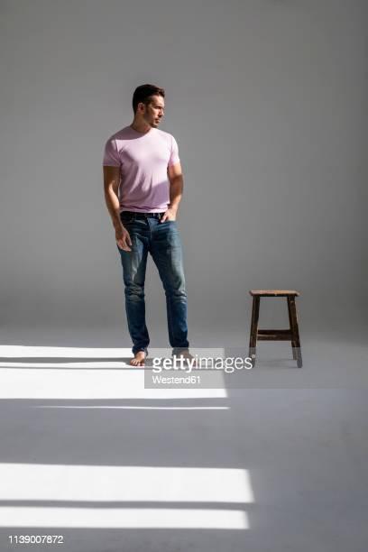 man standing in a loft in sunshine beside a stool - descalço imagens e fotografias de stock