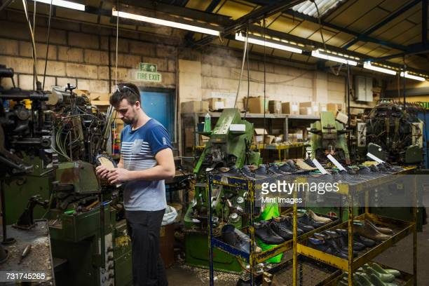 Man standing in a shoemakers workshop by a machine and holding a cycling shoe.