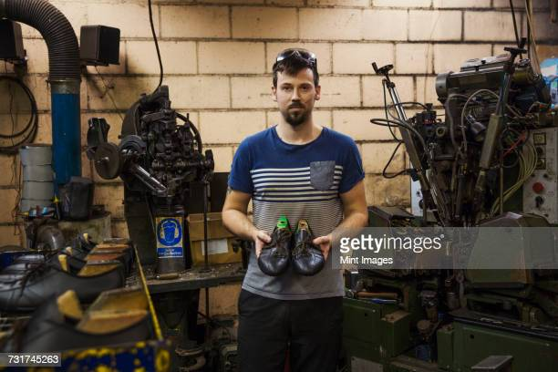 man standing in a shoemakers workshop, holding a pair of brown leather laced cycling shoes. - schuhmacher stock-fotos und bilder