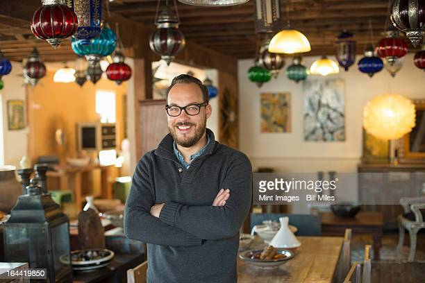 a man standing in a shop full of antique and decorative objects. antique shop displays. lighting, glass shades and furniture.  - antiquário loja - fotografias e filmes do acervo