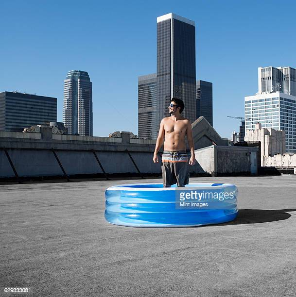 A man standing in a small inflatable water pool on a city rooftop.