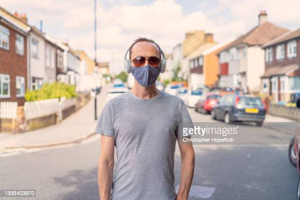 a man standing in a suburban street while wearing a face mask, sunglasses, and headphones - males stock pictures, royalty-free photos & images