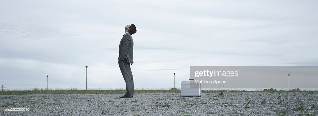 Man standing in abandoned lot looking up at sky, metallic briefcase on ground behind him : Stock Photo