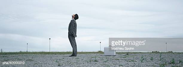 man standing in abandoned lot looking up at sky, metallic briefcase on ground behind him - the hobbit: an unexpected journey stock pictures, royalty-free photos & images