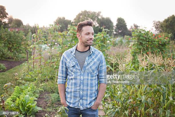 Man standing in allotment looking at his land