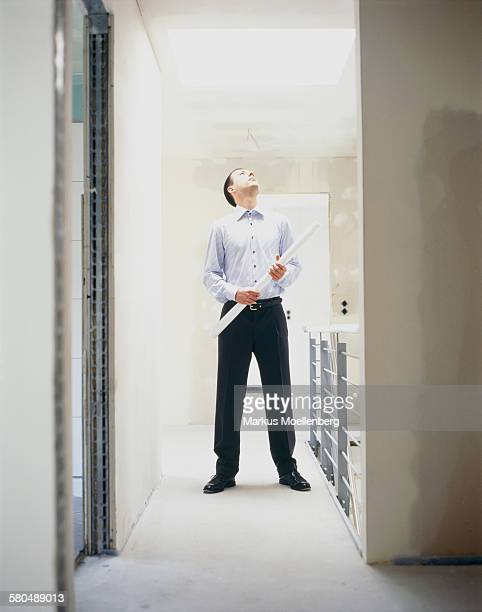Man standing in apartment, looking to skylight