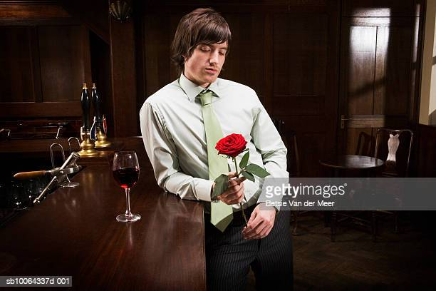 Man standing in bar looking at red rose