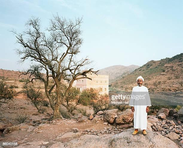 man standing in barren landscape - reportage foto e immagini stock