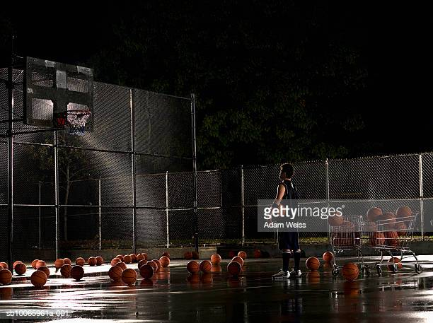 Man standing in basketball court at night