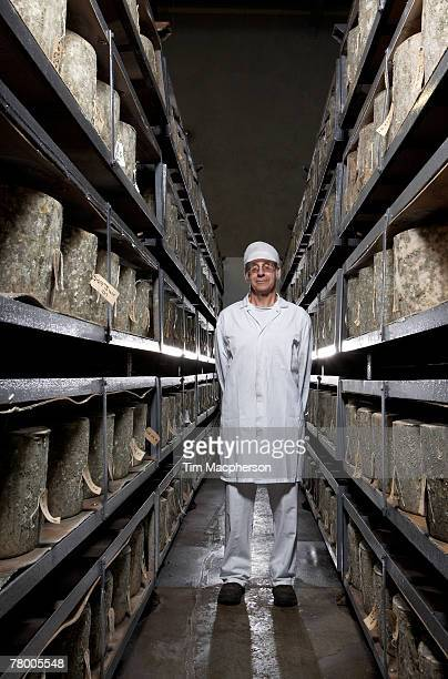 Man standing in between two shelves of cheeses.