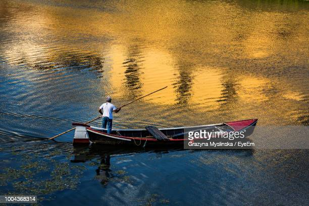 Man Standing In Boat On Lake
