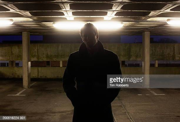 Man standing in carpark in shadow at night, upper half