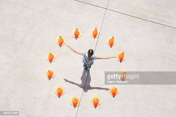 Man standing in circle of traffic cones with arms up