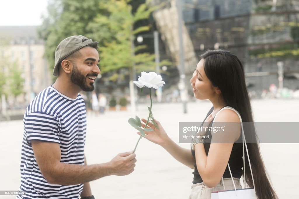 Man standing in city square giving his girlfriend a white rose : Stock Photo