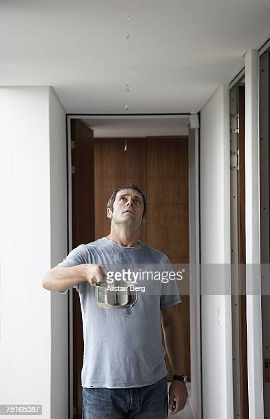 Man standing in corridor, holding saucepan under leak in ceiling, looking up