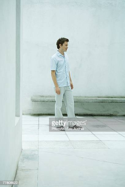 Man standing in courtyard, looking away, full length portrait