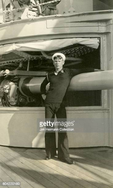 Man standing in deck of ship with arm draped over military equipment