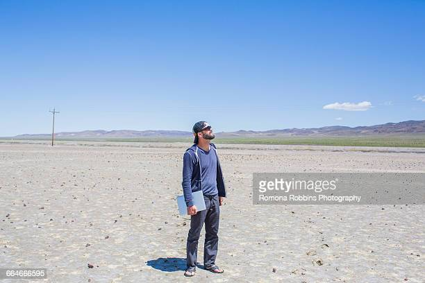 Man standing in desert holding laptop looking up, Nevada, USA