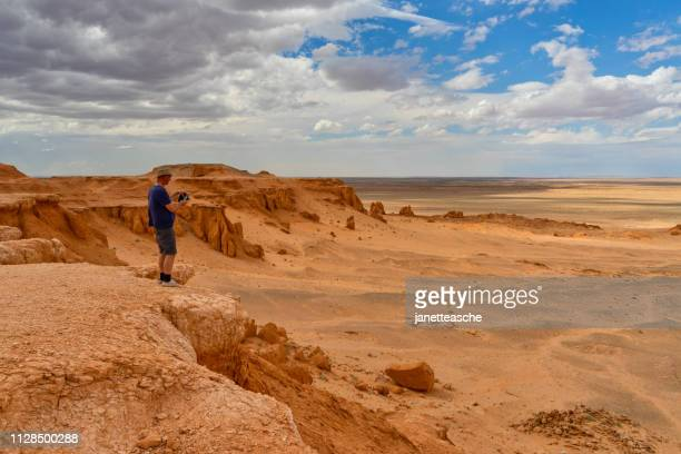 man standing in desert taking a photo, flaming cliffs, gobi desert, bulgan, mongolia - omnogov stock pictures, royalty-free photos & images