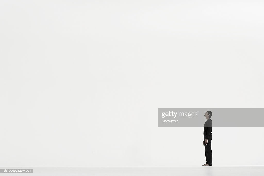 Man standing in distance against white background, side view : Stockfoto