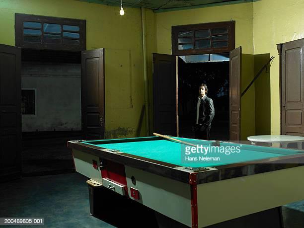 Man standing in doorway of billiard parlor