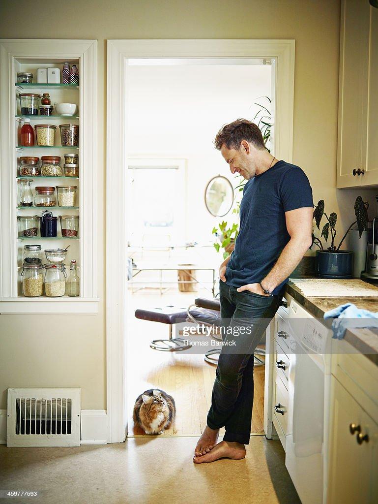 Man standing in doorway of kitchen looking at cat : Stock Photo