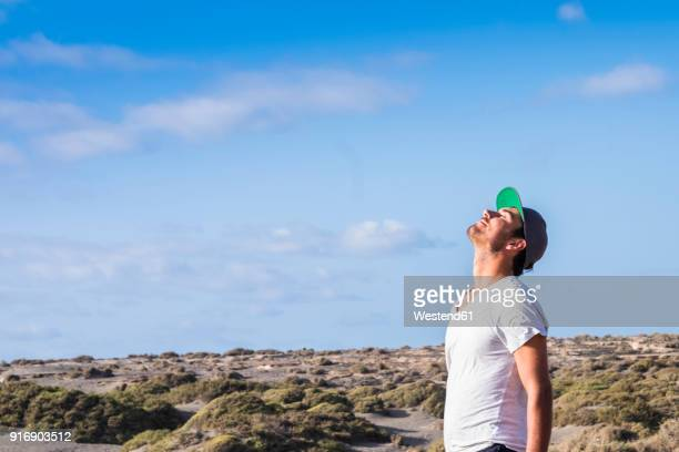 man standing in dune landscape with closed eyes - baseball cap stock pictures, royalty-free photos & images
