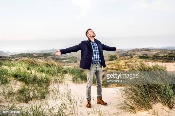 man standing in dunes with outstretched arms - 防寒着 ストックフォトと画像