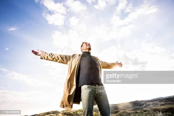man standing in dunes with outstretched arms - les bras écartés photos et images de collection
