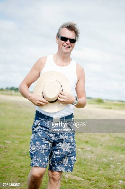 Man standing in field and holding his sun hat