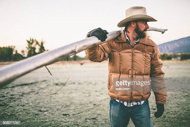 Man standing in field carries irrigation pipe over shoulder