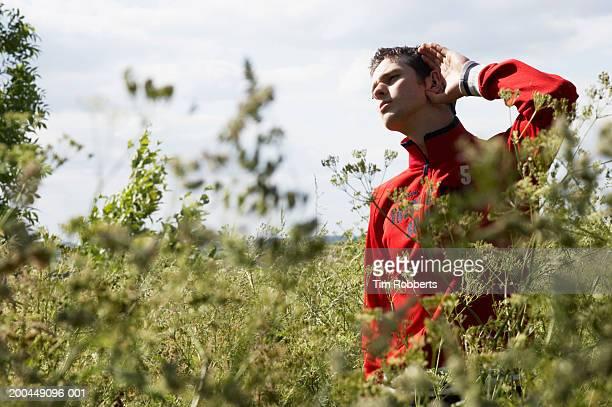 Man standing in field, cupping ear