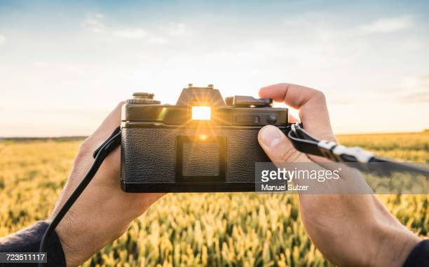 Man standing in field, holding SLR camera, sunlight shining through viewfinder, Neulingen, Baden-Wrttemberg, Germany