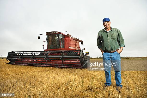 Man standing in field with plow
