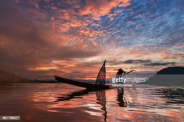 Man standing in fishing boat at sunset, Mekong river, Thailand