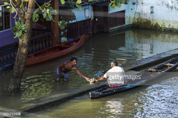 A man standing in floodwater shares a tray of tea with another man sitting in a canoe in Kainakary village in the district of Alappuzha Kerala India...