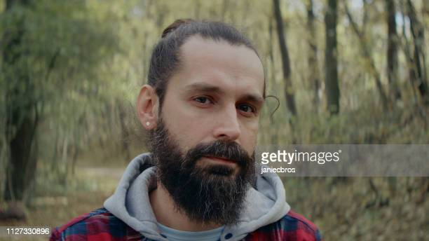 man standing in forest. portrait - man bun stock pictures, royalty-free photos & images