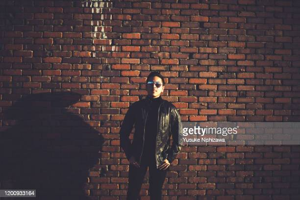 a man standing in front of a brick wall - yusuke nishizawa stock pictures, royalty-free photos & images