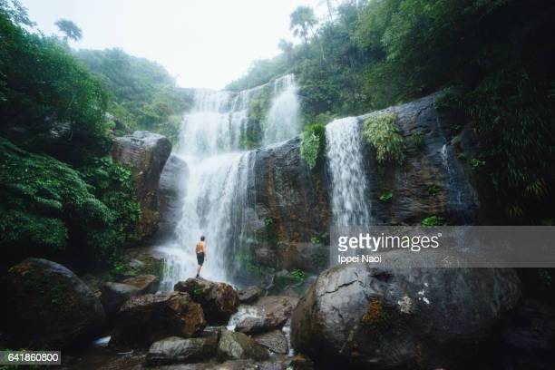 Man standing in front of a jungle waterfall, Iriomote, Japan