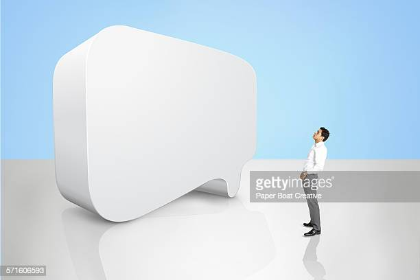 man standing in front of a large 3d speech bubble